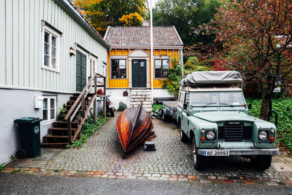 Trondheim, Norway - Old Range Rover and a boat parked in the street of Bakklandet wooden buildings district
